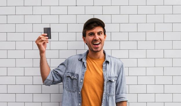 Hombre sonriente que sostiene el coche en el fondo de la pared