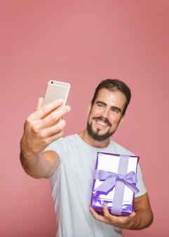 Hombre sonriente que sostiene la caja de regalo púrpura que toma el selfie del teléfono móvil