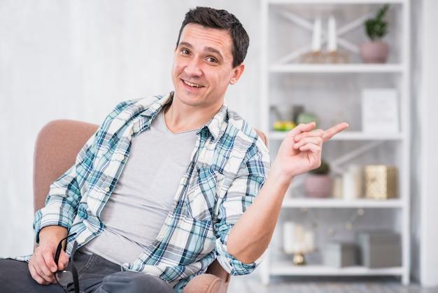 Hombre sonriente que sostiene las lentes y que señala lejos en silla en casa