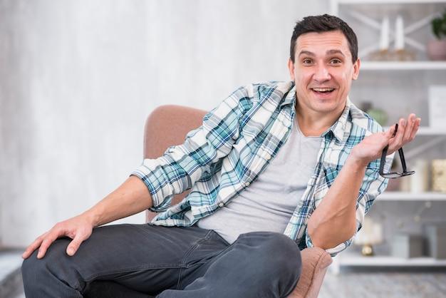 Hombre sonriente que sostiene las lentes en silla en casa
