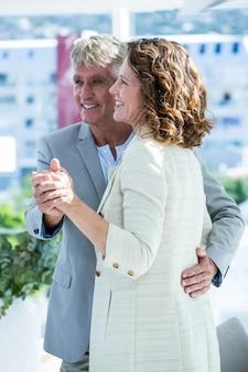 Hombre sonriente que sostiene la mano de la mujer