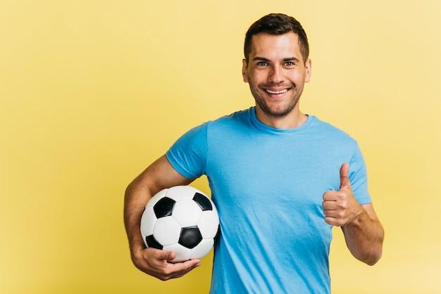 Hombre sonriente que sostiene una pelota de fútbol