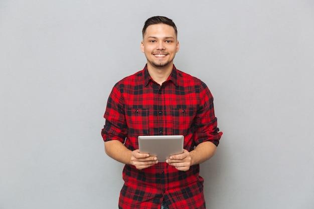 Hombre sonriente que sostiene la tableta y mirando a la cámara