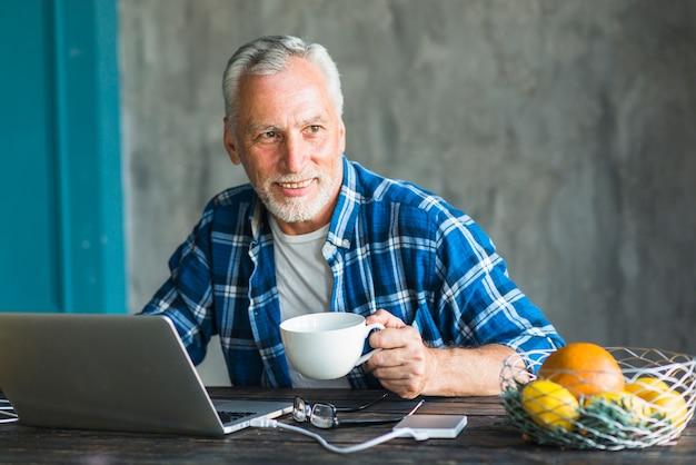 Hombre sonriente que sostiene la taza de café que mira lejos con la computadora portátil en la tabla