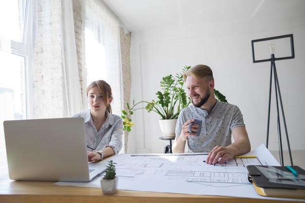 Hombre sonriente que sostiene la taza de café que mira el ordenador portátil usando a su compañero de trabajo femenino en la oficina