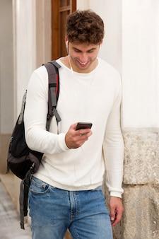 Hombre sonriente que sostiene el teléfono celular con el bolso y los auriculares