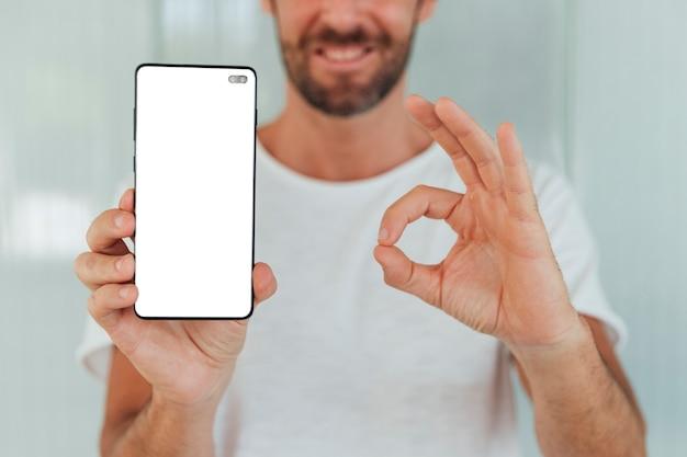 Hombre sonriente que sostiene el teléfono con maqueta