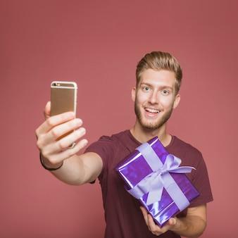 Hombre sonriente que toma el autorretrato del móvil que sostiene la caja de regalo