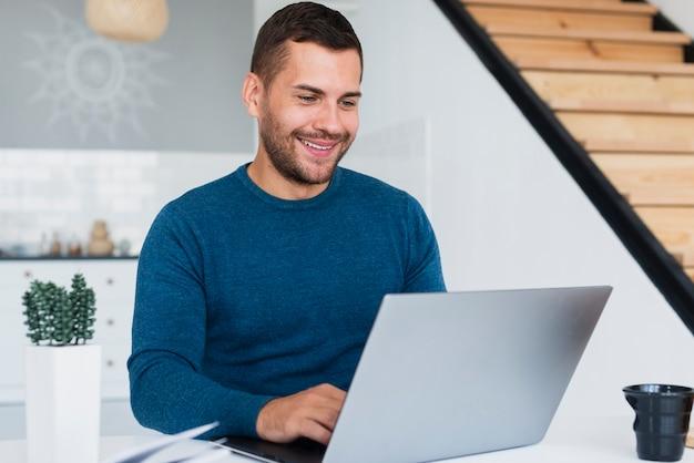 Hombre sonriente que trabaja en la computadora portátil en casa