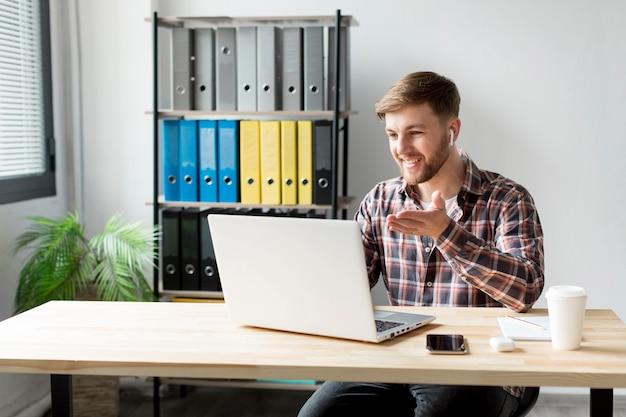 Hombre sonriente que trabaja en la computadora portátil