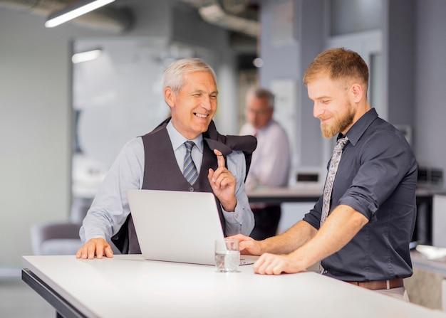 Hombre sonriente que usa la computadora portátil que se coloca con su encargado en el lugar de trabajo