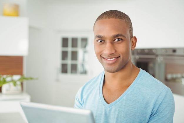 Hombre sonriente que usa la tableta en la cocina