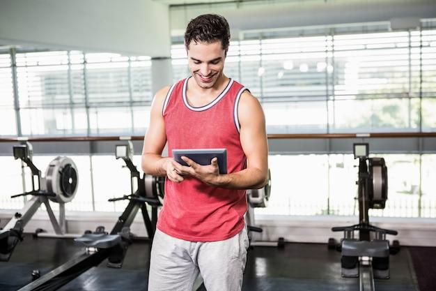 Hombre sonriente que usa la tableta en el gimnasio