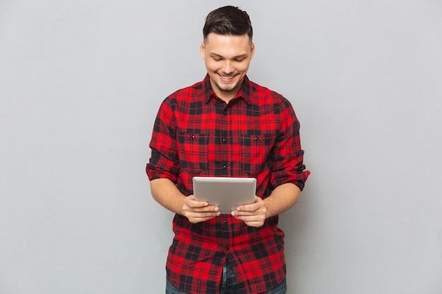Hombre sonriente que usa la tableta