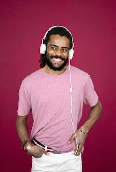 Hombre sonriente con rastas con auriculares