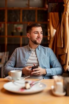 Hombre sonriente en el restaurante con teléfono