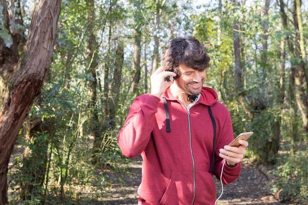 Hombre sonriente revisando su móvil