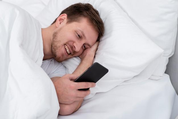 Hombre sonriente revisando sus mensajes