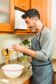 Hombre sonriente rompiendo un huevo en el tazón grande blanco