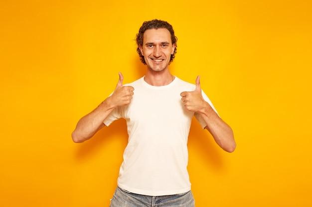 Hombre sonriente en ropa casual da pulgar hacia arriba como señal de que todo está bien, pone me gusta espacio para texto