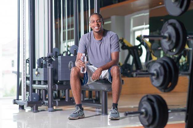 Hombre sonriente sentado en el gimnasio, sosteniendo una botella de agua
