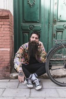 Hombre sonriente sentado en la puerta de entrada antigua hablando por teléfono móvil