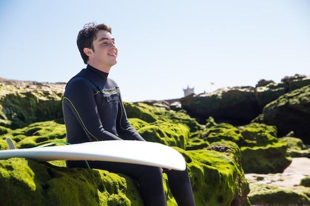 Hombre sonriente sentado en rocas cubiertas de musgo con tabla de surf