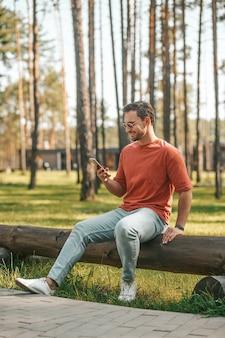 Hombre sonriente con smartphone sentado en la naturaleza