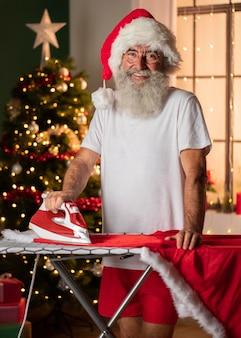 Hombre sonriente con sombrero de santa planchando su traje