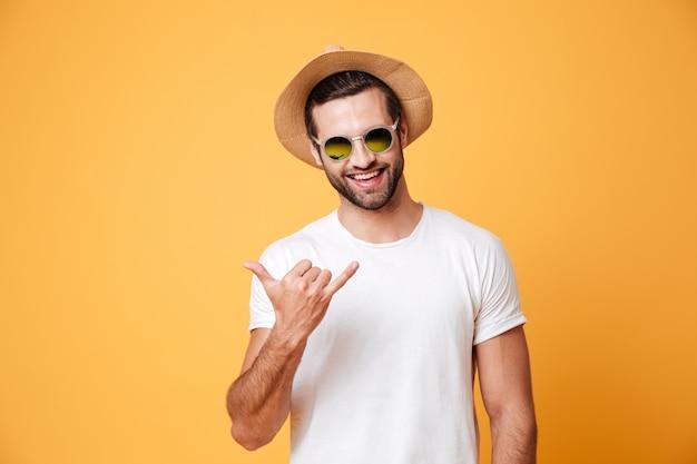 Hombre sonriente en sombrero de verano mirando cámara aislada gesticular