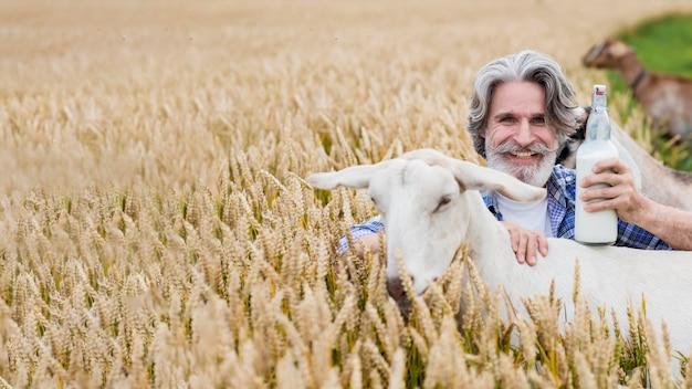 Hombre sonriente sosteniendo una botella de leche de cabra