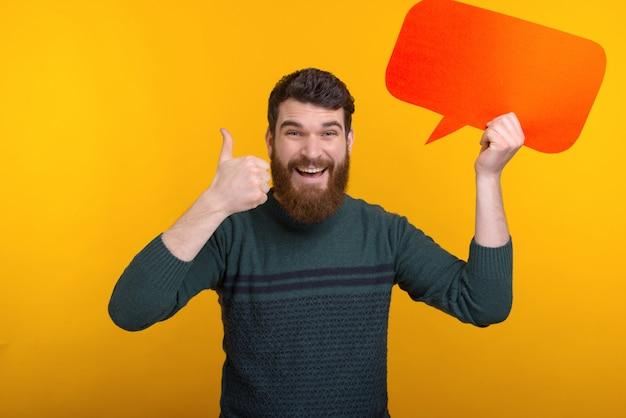 El hombre sonriente está sosteniendo un discurso anaranjado de la burbuja y está mostrando como gesto.