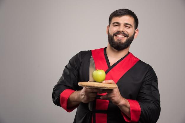 Hombre sonriente sosteniendo una manzana con un cuchillo sobre tabla de madera.