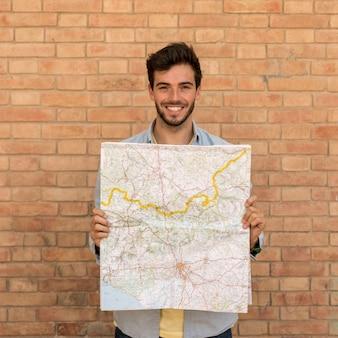 Hombre sonriente sosteniendo un mapa abierto