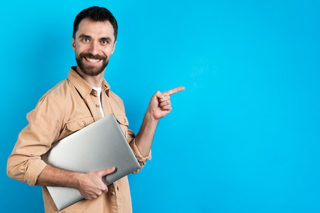 Hombre sonriente sosteniendo portátil y señalando