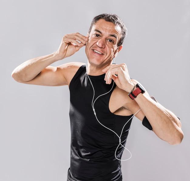 Hombre sonriente sporitve con auriculares