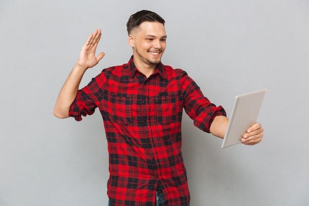 Hombre sonriente con tablet pc y saludando a la cámara