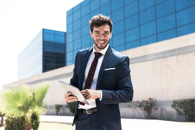 Hombre sonriente con tableta mirando a la cámara