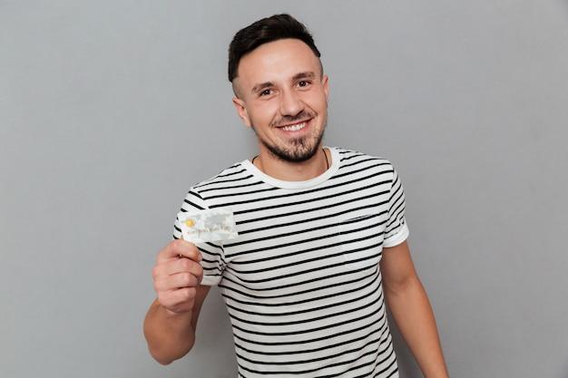 Hombre sonriente con tarjeta de crédito y mirando a cámara