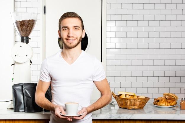 Hombre sonriente con una taza de capuchino en sus manos