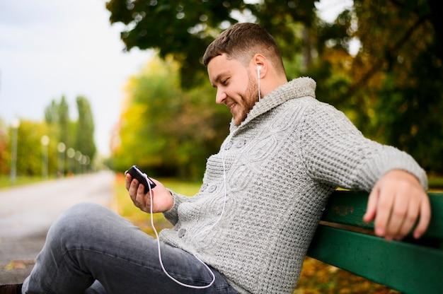 Hombre sonriente con teléfono inteligente y auriculares en un banco
