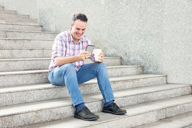Hombre sonriente con teléfono inteligente y bebida en la escalera