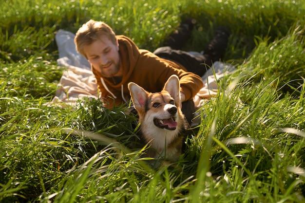 Hombre sonriente de tiro completo con perro en la naturaleza