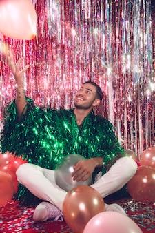 Hombre sonriente de tiro completo posando con globos