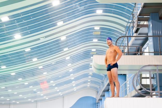 Hombre sonriente de tiro largo en el trampolín de la piscina