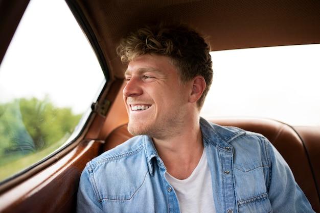 Hombre sonriente de tiro medio en coche