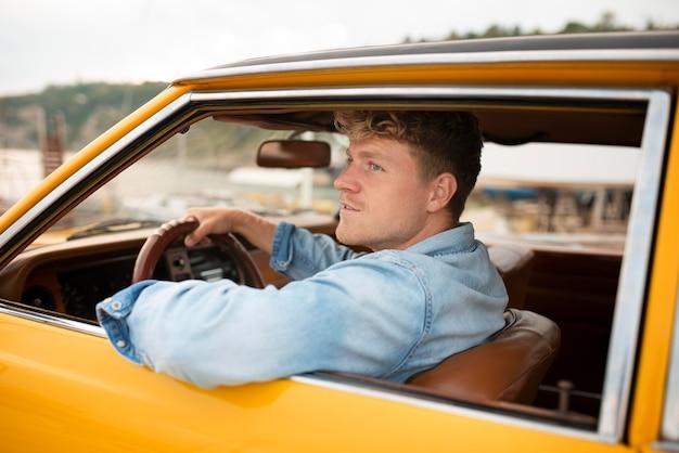 Hombre sonriente de tiro medio conduciendo coche