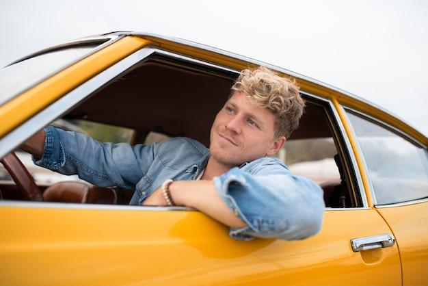 Hombre sonriente de tiro medio conduciendo