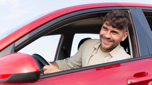 Hombre sonriente de tiro medio dentro del coche