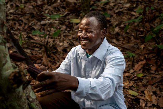 Hombre sonriente de tiro medio recogiendo granos de cacao